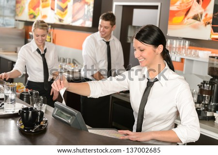 Female cashier giving receipt colleagues working in cafe - stock photo