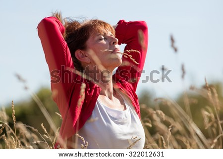 female casual relaxation - meditating mature woman enjoying fresh air in her hair with flower in her mouth in long dry summer field seeking for peace,summer daylight - stock photo
