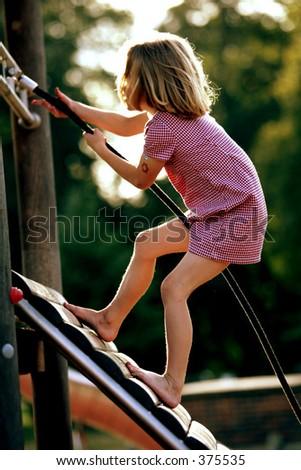 female caucasian child climbing up a wooden climbing frame - stock photo
