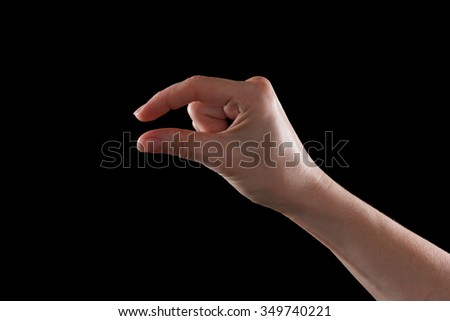 Female caucasian hand gesturing a small amount, isolated on black. - stock photo