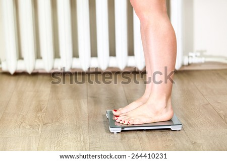 Female Caucasian legs standing on weight scale - stock photo
