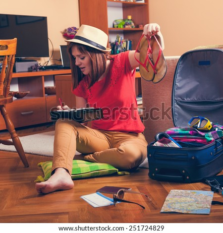 Female Checking Are There In Suitcase All Of Stuff From Packing List - stock photo