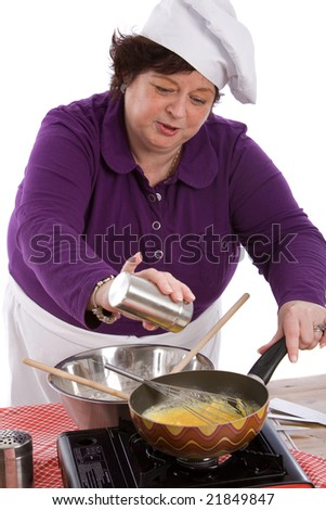 Female chef adding some salt to her mixture in the wok - stock photo