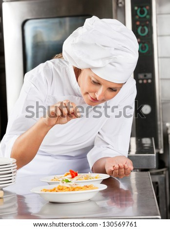 Female chef adding spices to dish at commercial kitchen counter - stock photo