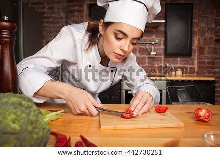 Female chef cook cutting vegetables in the kitchen  preparing a meal from tomatoes and broccoli - stock photo