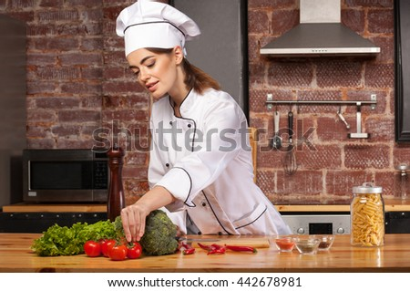 Female chef cook in a white hat in the kitchen preparing a meal with pasta, salad, broccoli, tomatoes and pepper - stock photo