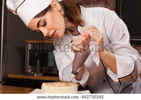 Female chef cook preparing a sweet cake in the kitchen, pouring the chocolate cream on it - stock photo