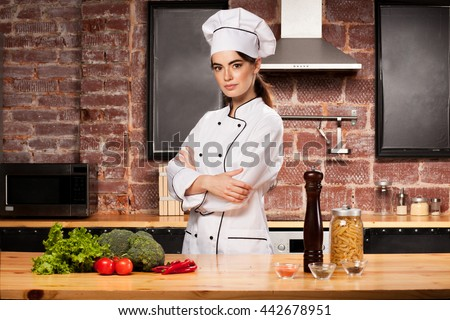 Female chef cook standing in the kitchen near wooden table with pasta, salad, broccoli, tomatoes, pepper, pepper mill and spices - stock photo