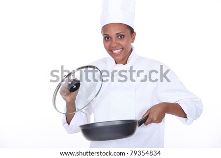 female chef exhibits a frying pan - stock photo