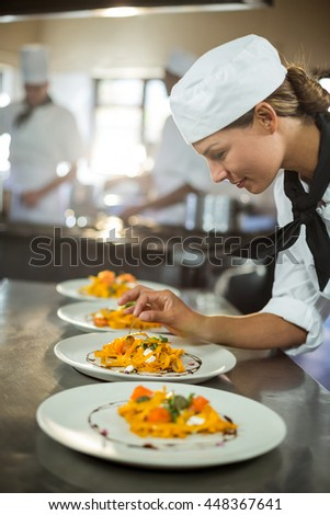 Female chef garnishing plate of food in commercial kitchen - stock photo