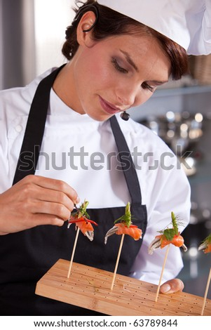 Female chef giving a cooking demonstration adding a drop of balsamico to her dish - stock photo