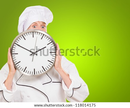 female chef hiding behind a clock against a green background - stock photo
