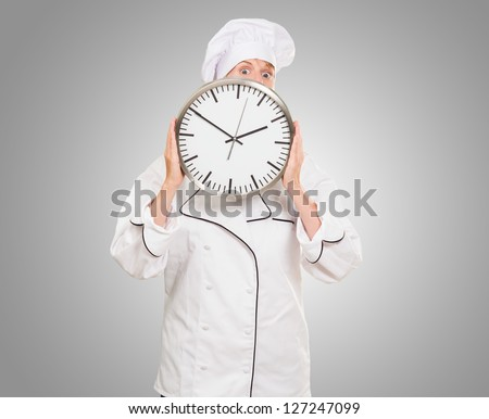 female chef hiding behind a clock against a grey background