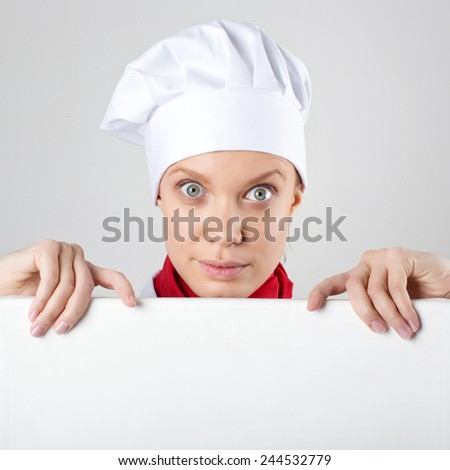 Female chef holding a poster for text, look at the poster and smiling on a white background