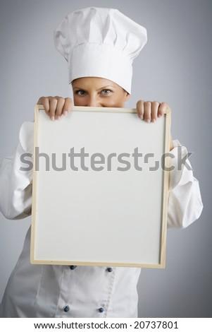 female  chef holding menu board - stock photo
