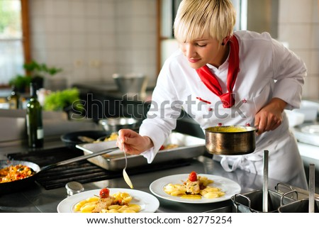 Female chef in a restaurant or hotel kitchen cooking delicious food, she is decorating the dishes - stock photo