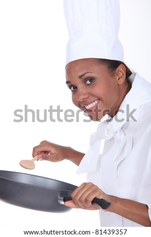 Female chef in uniform with a deep frying pan and wooden spoon - stock photo