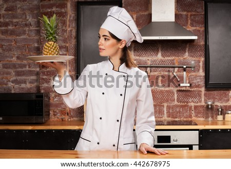 Female chef in white cap and uniform with pineapple on the plate in her hands - stock photo