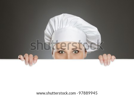 Female chef looking over paper sign billboard - stock photo