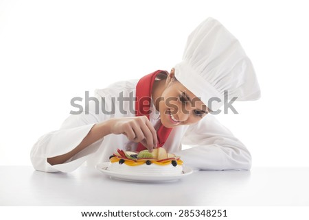 Female chef making mixed fruit cake isolated over white background - stock photo