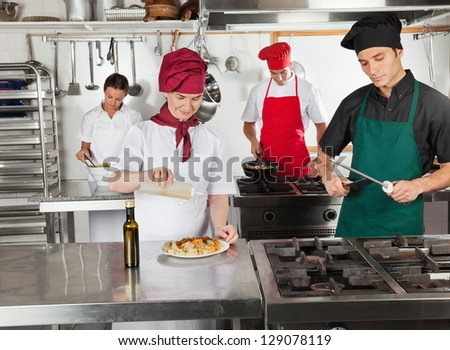 Female chef pouring oil in dish with colleagues working in restaurant kitchen - stock photo