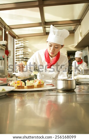 Female chef preparing a strawberry tart in a restaurant with a chef standing in the background - stock photo