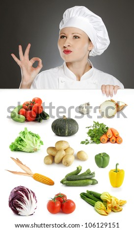 Female chef showing positive gesture over vegetable collection - stock photo
