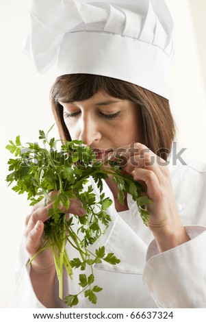 Female Chef Smelling Parsley, white background