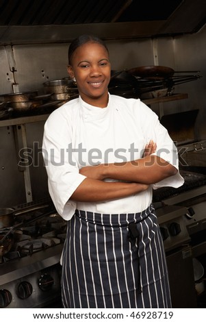 Female Chef Standing Next To Cooker In Restaurant Kitchen - stock photo