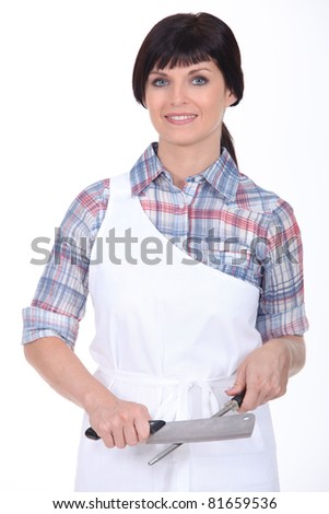 Female chef stood with knife and sharpener