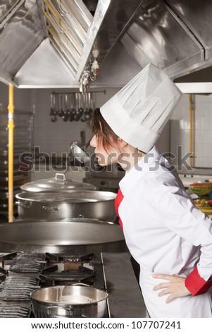 female chef tasting sauce - stock photo