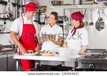 Female chef with colleagues looking for recipe on a tablet computer while cooking at kitchen - stock photo