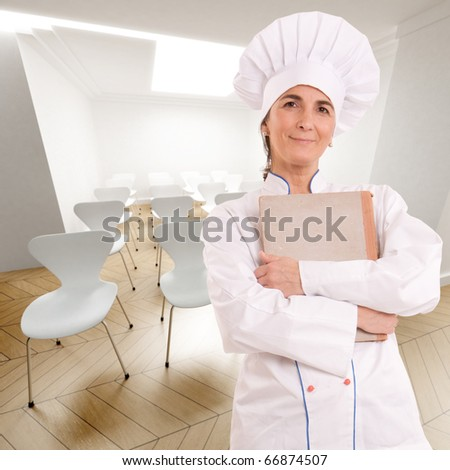 Female chef with old book in a conference room - stock photo