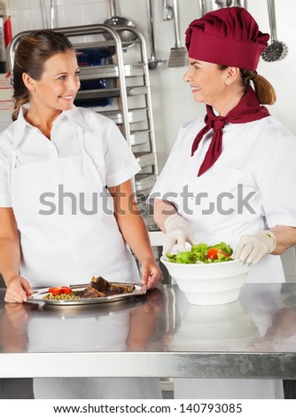 Female chefs with their dishes looking at each other in commercial kitchen - stock photo