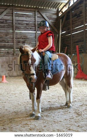 Female child mounted on small horse in indoor riding arena. - stock photo