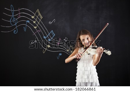 Female child playing the violin next to a blackboard - stock photo