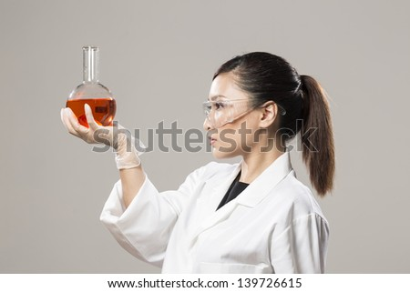 Female Chinese Healthcare professional or scientific researcher holding a round-bottomed flask