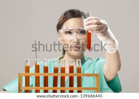 Female Chinese Healthcare professional or scientific researcher looking at a row of test tubes
