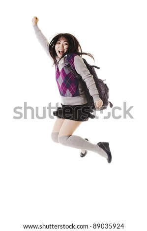 Female Chinese student with a backpack on a white background jumping in the air. - stock photo