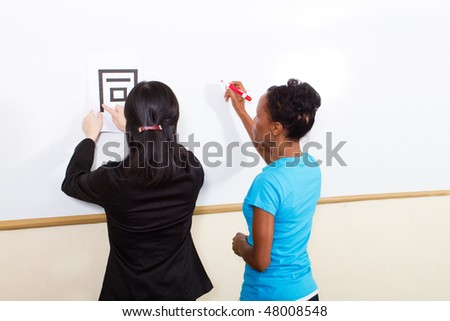female chinese teacher teaching chinese character in classroom - stock photo