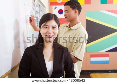 female chinese teacher teaching chinese to african student in classroom - stock photo