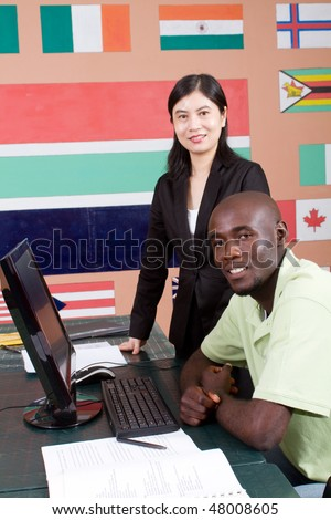 female chinese teacher teaching computer to african student - stock photo