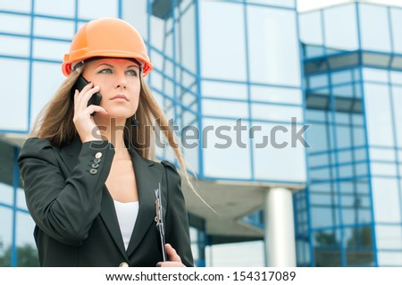 Female civil engineer talking on the phone building in the background