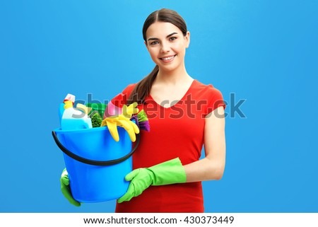 Female cleaner on blue background - stock photo
