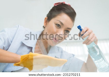 Female cleaner using spray to wipe the glass table, view from below - stock photo