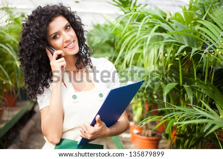 Female clerk talking on the phone in a greenhouse - stock photo