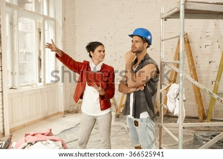 Female client and contractor talking at renovation site. - stock photo