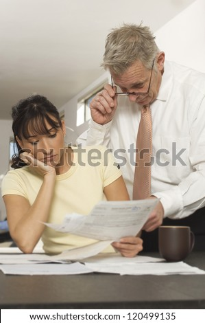 Female client holding document while senior financial adviser reading document in office