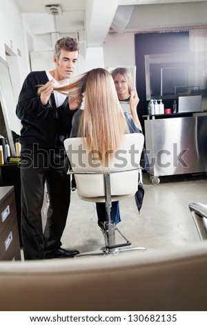Female client holding mirror while hairdresser styling her hair at parlor - stock photo