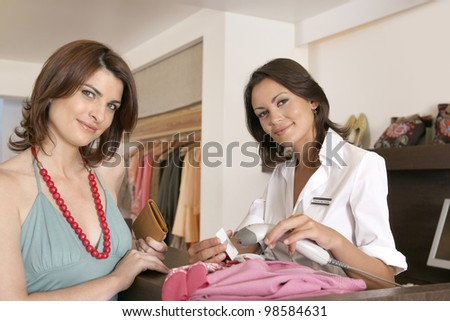 Female client shopping at fashion store with shop assistant reading a label with a bar code reader. - stock photo